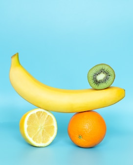 Równoważenie owoców na niebieskiej powierzchni. stos owoców banan, kiwi, pomarańcza, cytryna.