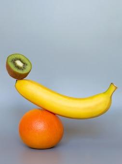 Równoważenie owoców na szarej powierzchni. stos owoców banan, kiwi, pomarańcza.