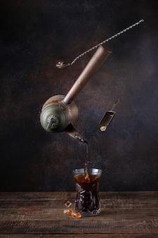 Równoważenie turka z nalewaniem kawy. cukier kandyzowany i łyżka barmańska. latające jedzenie. stół z drewna.