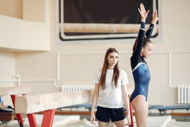Równoważnia gimnastyka dziecka. dziewczyna gimnastyczka sportowca podczas ćwiczeń na drążku poziomym w zawodach gimnastycznych. trener z dzieckiem.