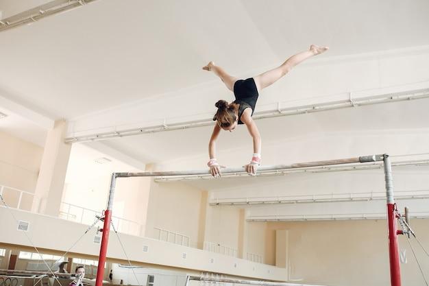 Równoważnia gimnastyka dziecka. dziewczyna gimnastyczka sportowca podczas ćwiczeń na drążku poziomym w zawodach gimnastycznych.