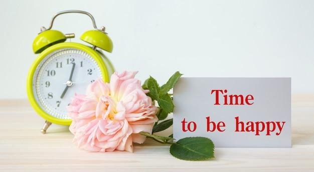 Róża, budzik i kartka na motywacyjny napis - czas na szczęście.