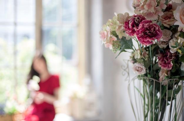 Róża dekoracji domu i rozmycie kobiety stojącej okno