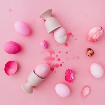 Róża i białe pisanki w pobliżu kubków jaj między odpryskami cieczy barwnika