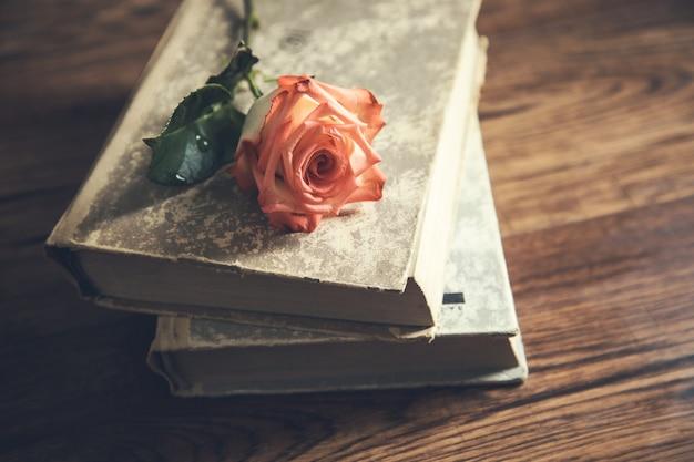 Róża na książkach na drewnianym stole