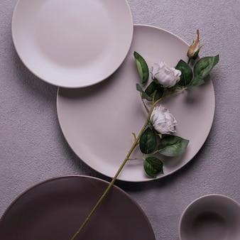 Róża na szarych talerzach. kwadratowa romantyczna kompozycja