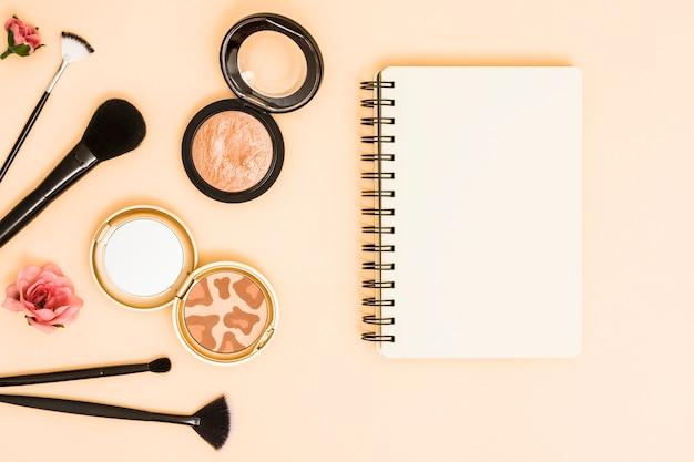 Róża; pędzle do makijażu i kompaktowy proszek w pobliżu notatnika spirali na beżowym tle