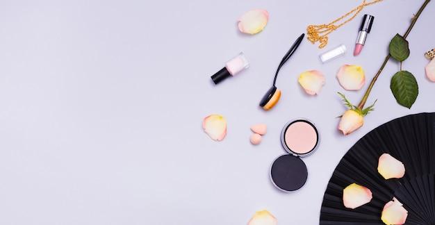 Róża; płatki; owalny pędzel; lakier do paznokci; szminka i naszyjnik na fioletowym tle