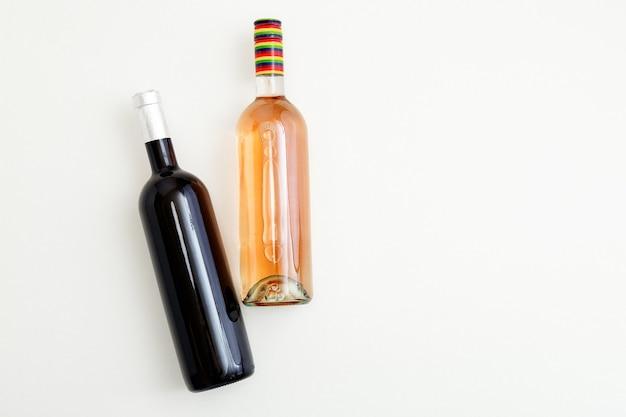 Różana butelka wina i czerwone wino 2 dwa minimalistyczne kompozycje wina widok z góry na białym tle