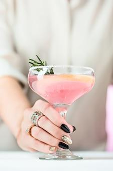 Różane egzotyczne koktajle i owoce oraz kobieca ręka