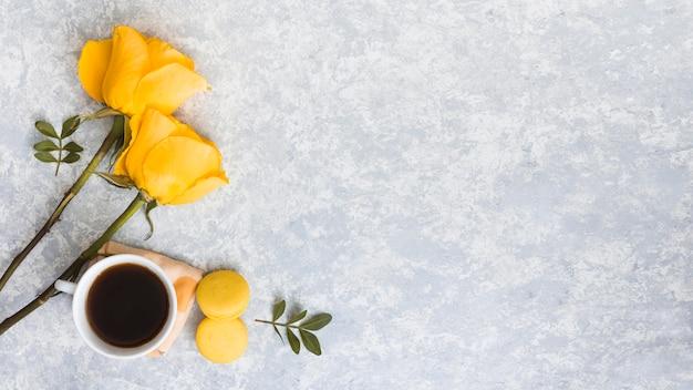 Różani kwiaty z macaroons i filiżanka kawy
