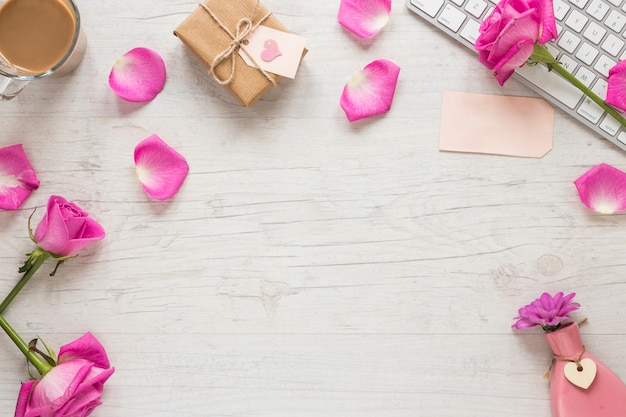 Różani kwiaty z prezenta pudełkiem i klawiaturą na stole
