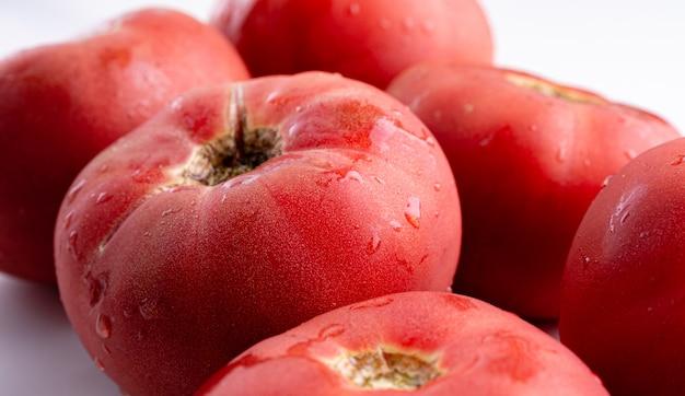 Różani pomidory zamykają up na bielu stole. jesienne lub letnie zbiory. świeża żywność ekologiczna z ogrodu