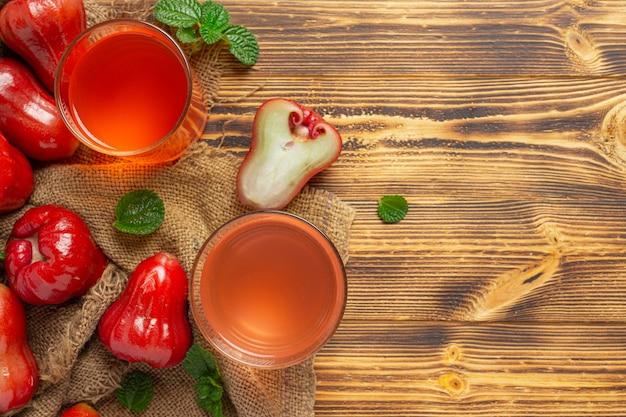 Różany sok jabłkowy na ciemnej powierzchni drewnianej