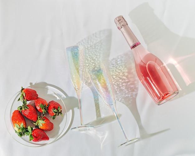 Różany szampan w butelce jasne kieliszki na wino i czerwone jagody truskawkowe musujące