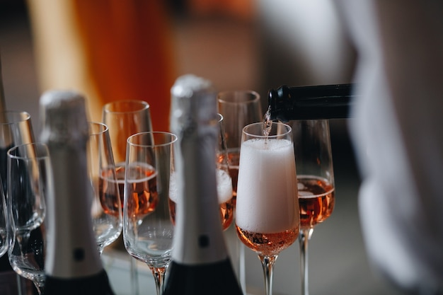 Różany szampan - wino musujące w kieliszkach; catering na przyjęciu weselnym lub podobnym wydarzeniu.