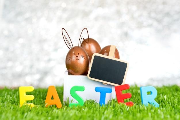 Różany złocisty easter jajko w drewnianym białym pudełku i pusta blackboard klamerka na zielonej trawy polu