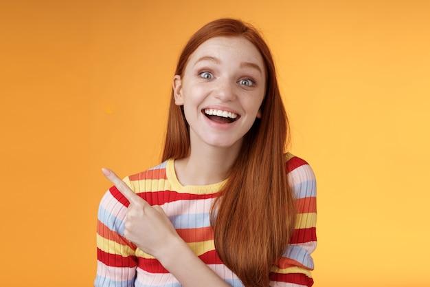 Rozbawiona beztroska, podekscytowana, emocjonalna rudowłosa fanka uwielbia mówić ulubiony film wskazując lewy górny róg zafascynowana uśmiechnięta szeroko szczęśliwa zachwycona uczestniczą w niesamowitej imprezie, pomarańczowe tło.
