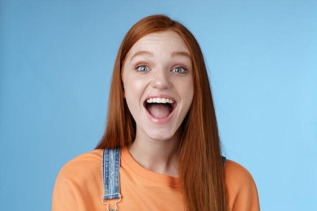 Rozbawiona, charyzmatyczna, żywa, wychodząca rudowłosa dziewczyna podekscytowana zabawą przyjaciele krzyczą, że pokazują idealny biały uśmiech ciesz się przyjazną, radosną atmosferą stojącą podekscytowany pozytywnym niebieskim tłem
