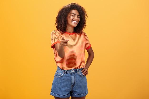 Rozbawiona ciemnoskóra kobieta z fryzurą afro, śmiejąca się z zamkniętymi oczami, wskazująca radośnie na aparat.