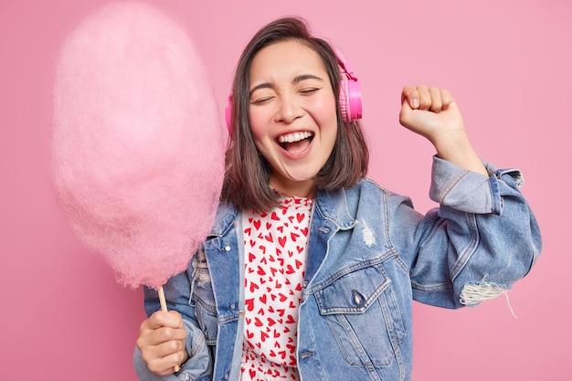 Rozbawiona ciemnowłosa nastolatka tańczy beztroskie ruchy w rytm muzyki słucha ulubionej piosenki przez słuchawki trzyma rękę podniesioną trzyma watę cukrową robi sobie słodki deser. styl życia.