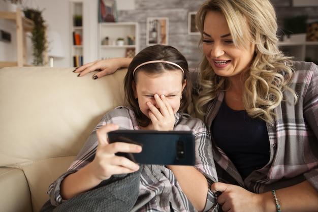 Rozbawiona dziewczynka w wieku przedszkolnym podczas korzystania ze smartfona siedząca na kanapie z matką.