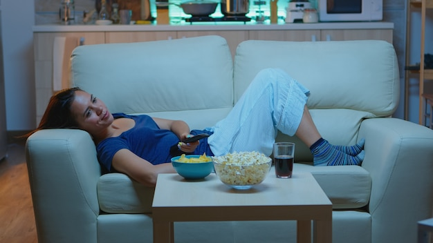 Rozbawiona gospodyni domowa za pomocą pilota, leżąc na kanapie, śmiejąc się i jedząc przekąski. szczęśliwa, zrelaksowana, samotna pani w piżamie ciesząc się wieczorem siedząc na wygodnej kanapie oglądając telewizję.