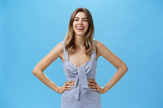 Rozbawiona i zachwycona śliczna dorosła kobieta o kasztanowych włosach w zwykłych ubraniach trzymająca się za ręce na biodrze, śmiejąca się i uśmiechnięta szeroko, podekscytowana podczas rozmowy pozującej na niebieskiej ścianie