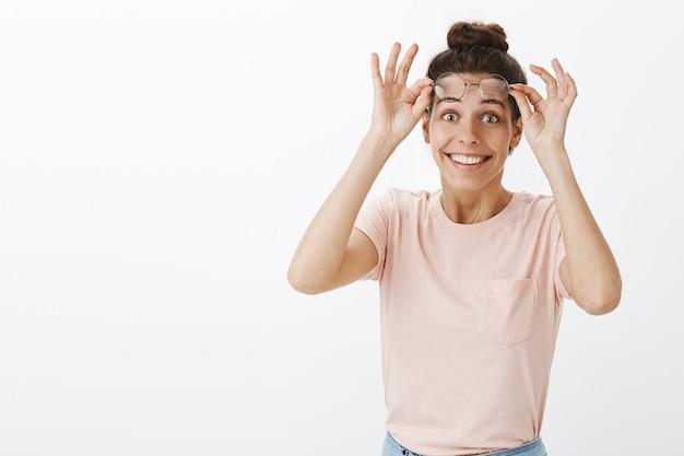 Rozbawiona i zdziwiona dziewczyna w okularach pozuje przy białej ścianie