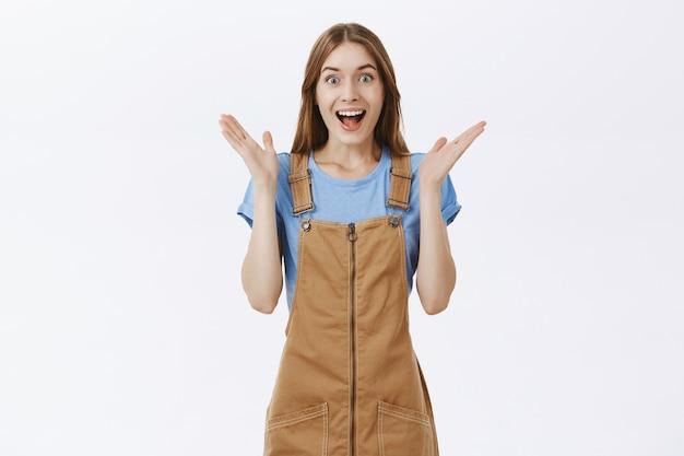 Rozbawiona i zdziwiona radosna dziewczyna radująca się wspaniałą nowiną, świętująca dobre wieści