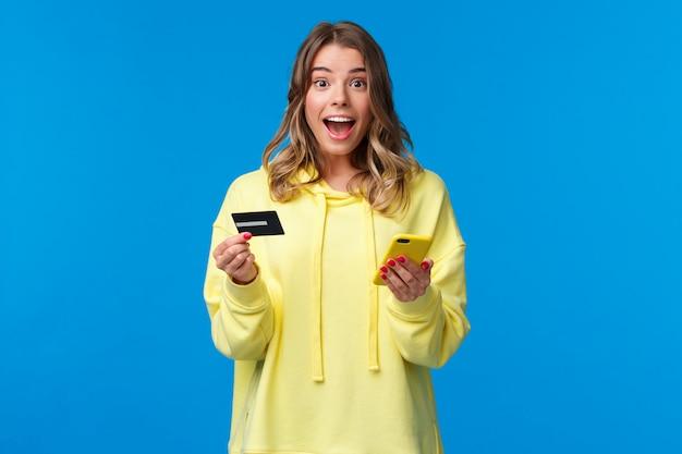 Rozbawiona i zdziwiona śliczna blond dziewczyna otrzymuje fajną ofertę cashback lub bankową po użyciu nowej karty kredytowej ze specjalną ofertą studencką, trzymając telefon komórkowy