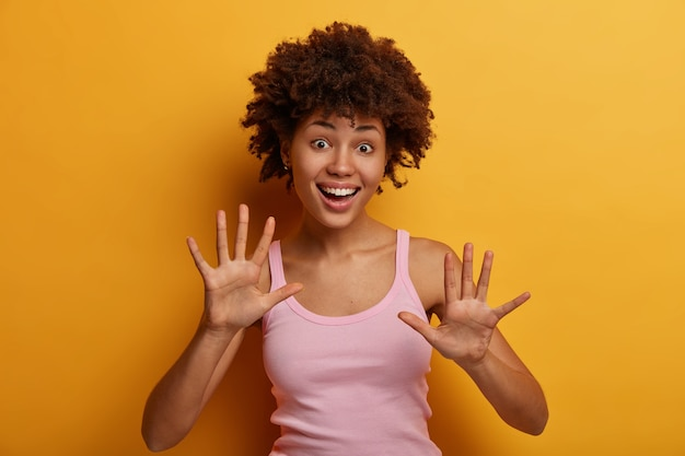 Rozbawiona, kręcona młoda kobieta podnosi dłonie i ma wesoły nastrój, wygłupia się, uśmiecha się radośnie, nosi luźną koszulkę, wyraża dobre emocje i szczere uczucia, odizolowana na żółtej ścianie