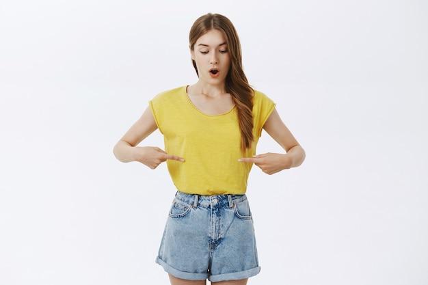 Rozbawiona ładna dziewczyna wskazująca na swój brzuch ze zdumieniem