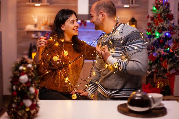 Rozbawiona para bawi się światłem choinkowym dekorującym kuchnię
