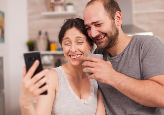 Rozbawiona para patrząc na telefon rano podczas śniadania. radosny żonaty mąż i żona robiąc śmieszne miny podczas robienia zdjęć podczas śniadania w kuchni.