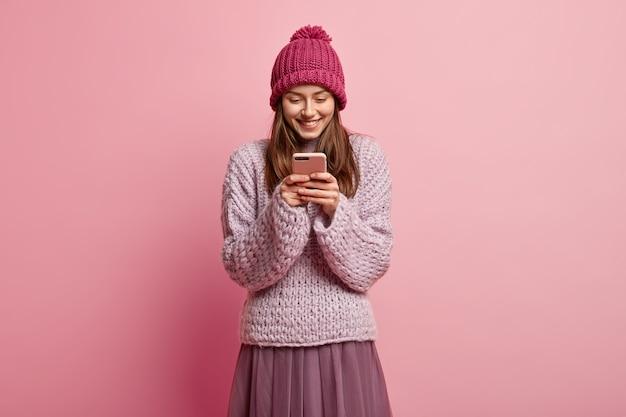 Rozbawiona, radosna, zadowolona młoda kobieta trzyma smartfona, nosi czapkę zimową i sweter z dzianiny