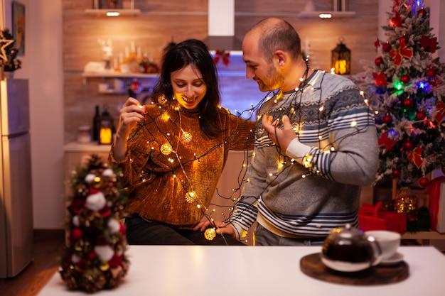 Rozbawiona romantyczna para bawiąca się lampką choinkową dekorującą świąteczną kuchnię