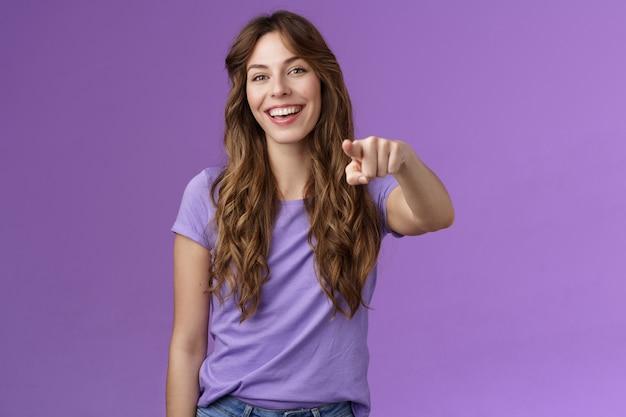 Rozbawiona rozbawiona atrakcyjna żywa dziewczyna kręcona fryzura śmiejąca się szczęśliwie wskazująca palcem wskazująca aparat fotograficzny dokonaj wyboru uśmiechając się szeroko pewni, że decyzja właściwa stoi na fioletowym tle.