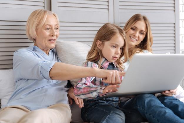 Rozbawiona starsza pani siedząca obok wnuka i córki na łóżku i wskazująca na ekran laptopa, podczas gdy jej wnuczka coś pisze