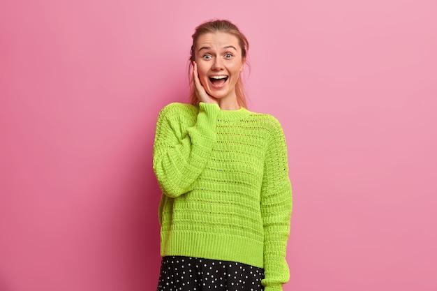 Rozbawiona, szczęśliwa europejka śmieje się głośno, jest podekscytowana i bardzo zadowolona, trzyma rękę na policzku, wstaje optymistycznie, ubrana w za duży dzianinowy sweter