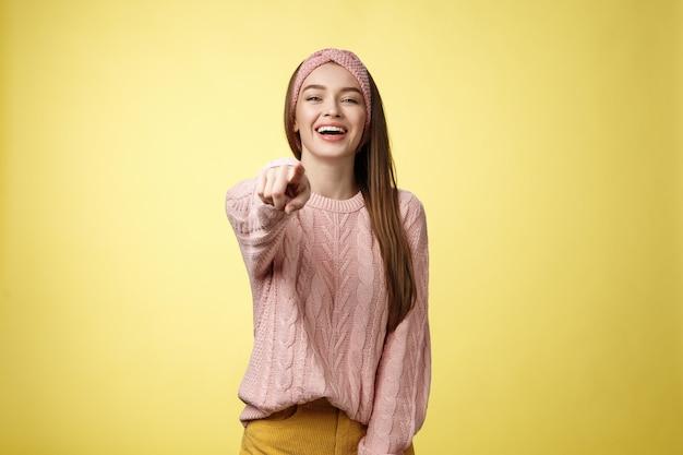Rozbawiona urocza delikatna młoda europejka dziewczyna szydzi z zabawy z kimś wskazującym palcem na...