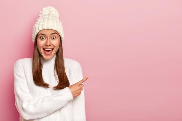 Rozbawiona wesoła kobieta wskazuje palcem wskazującym, nosi biały kapelusz i sweter, lubi ciekawą scenę, ma długie proste włosy, uśmiecha się i pokazuje miejsce na kopię