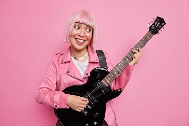 Rozbawiona wesoła różowowłosa gwiazda rocka gra na gitarze elektrycznej będąc częścią zespołu ubranego w kurtkę, gotowego do występu na scenie, wykonuje nowe pozy piosenki w pomieszczeniu. koncepcja hobby rozrywki muzycznej