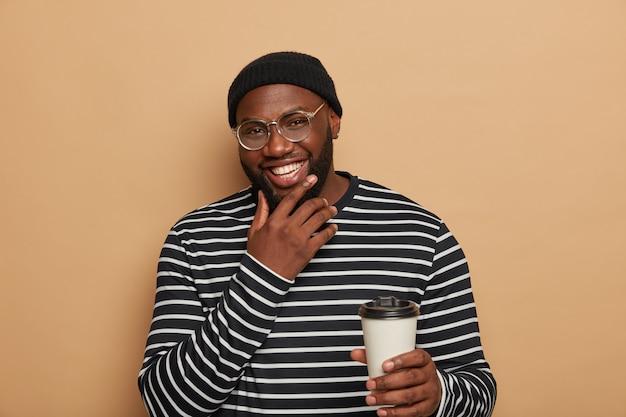 Rozbawiony afroamerykanin z zębatym uśmiechem, gęstą brodą, nosi sweter w paski, lubi pić kawę na wynos