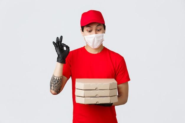 Rozbawiony azjatycki mężczyzna w czerwonym mundurze, czapce i koszulce, noszący rękawice ochronne i maskę medyczną dla bezpieczeństwa klienta, dostarczający jedzenie na wyciągnięcie ręki, przynoszący pizzę, pokazujący dobry znak i wpatrujący się w smaczną pizzę