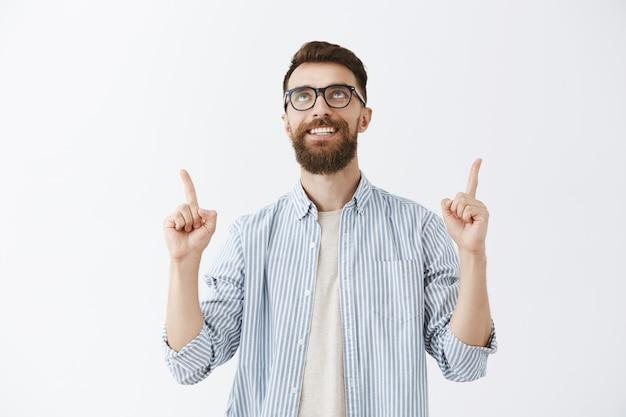 Rozbawiony przystojny brodaty mężczyzna pozuje przy białej ścianie