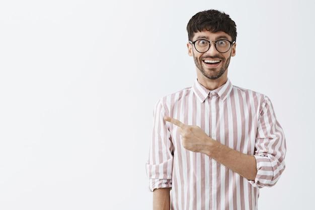 Rozbawiony stylowy brodaty facet pozujący przy białej ścianie w okularach