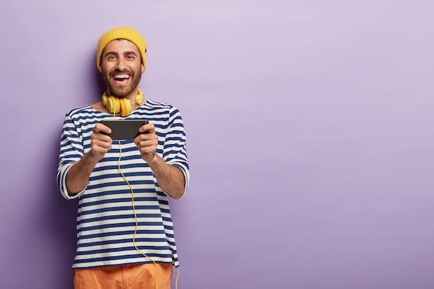 Rozbawiony, zabawny facet gra w gry wideo przez sieć komórkową, ubrany w zwykłe ciuchy, pozytywnie się uśmiecha, nosi słuchawki na szyi