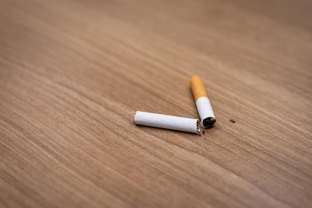 Rozbijanie papierosów na stole dla koncepcji rzucenia palenia.