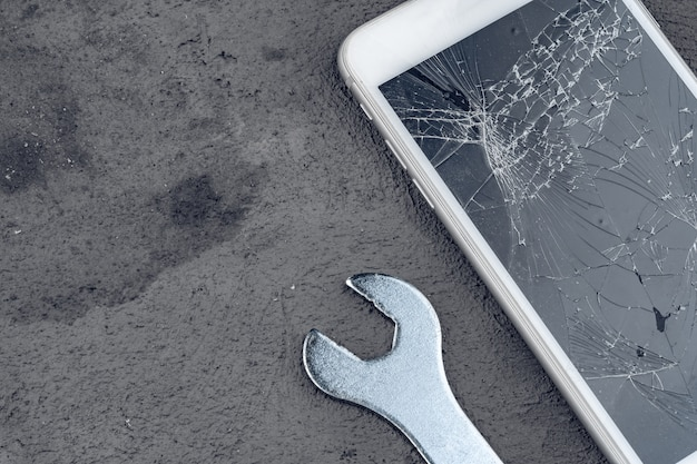 Rozbił się smartfon z narzędzi do naprawy na szarym tle